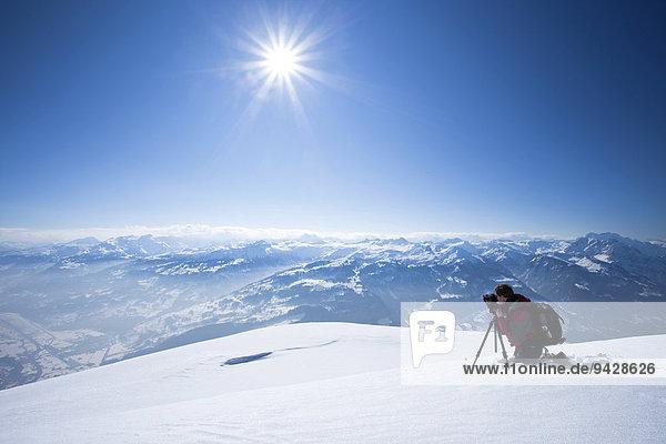 Fotograf beim Fotografieren mit Stativ in den verschneiten Alpen am Chäserrugg im Toggenburg  Schweiz  Europa