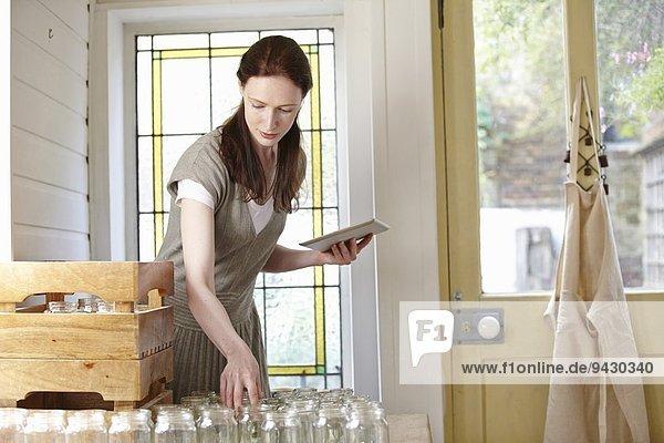 Imker mit digitaler Tablette in der Küche bei der Zubereitung von Gläsern