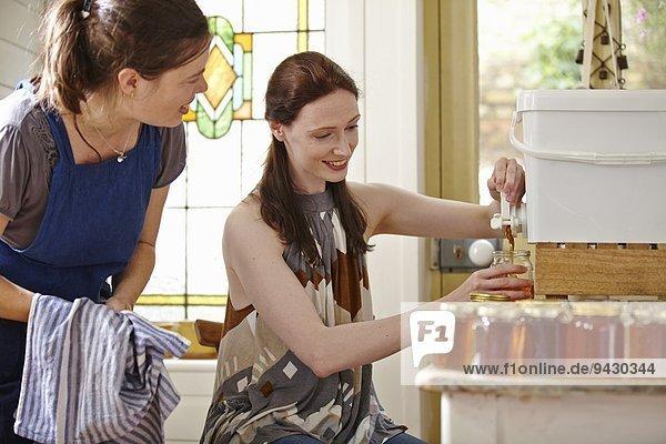 Imkerinnen in der Küche  Abfüllung von gefiltertem Honig aus Bienenstock