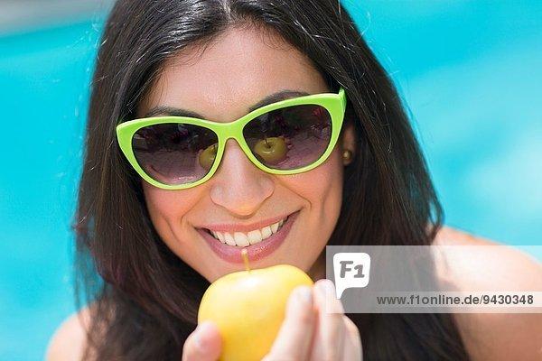 Porträt einer jungen Frau am Pool  die den Apfel hochhält.