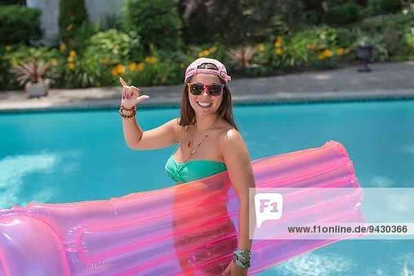Porträt einer jungen Frau  die ein loses Schild am Pool aufhängt.