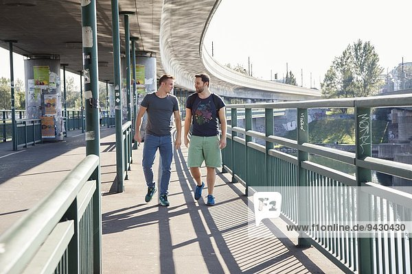 Two young men chatting as they walk over bridge