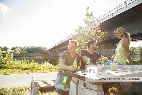 Three young friends drinking beer on riverside picnic bench