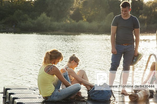 Three young adult friends tying shoelaces on riverside pier