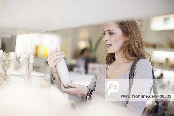 Frau beim Durchstöbern von Produkten im Verkaufsregal