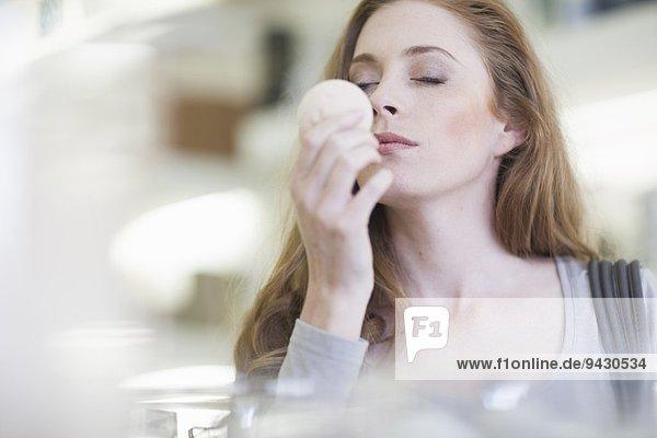 Frau riecht Produkt aus dem Verkaufsregal