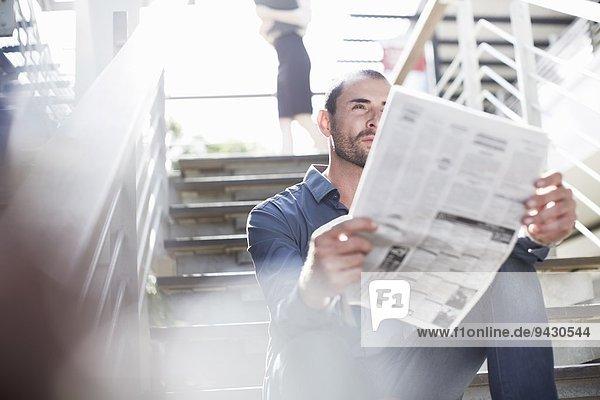 Geschäftsmann beim Zeitungslesen auf der Treppe
