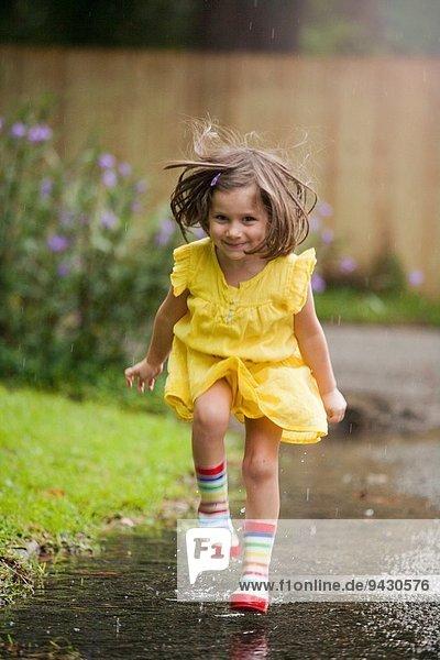 Mädchen mit Gummistiefeln in der Regenpfütze