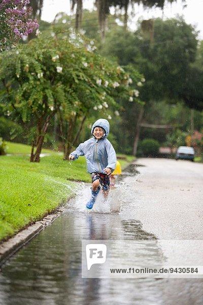 Junge in Gummistiefeln läuft und spritzt in Regenpfütze
