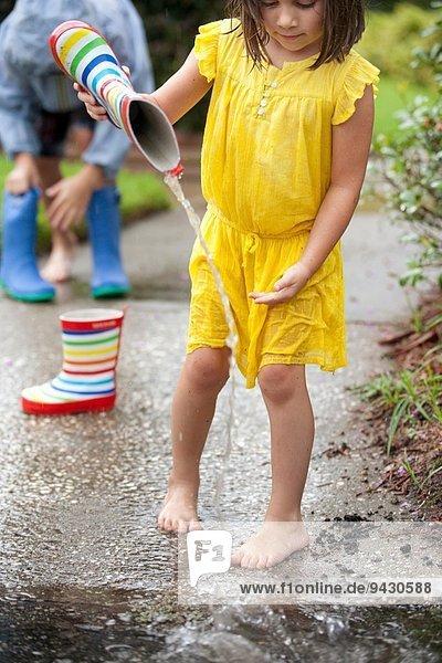 Mädchen gießt Wasser aus Gummistiefeln in die Regenpfütze
