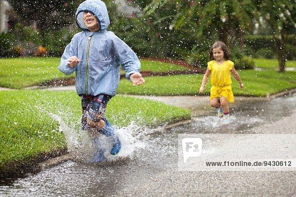 Junge und Schwester in Gummistiefeln laufen und planschen in der Regenpfütze