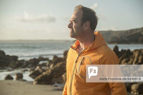 Erwachsener Mann  am Strand stehend  mit Blick aufs Meer