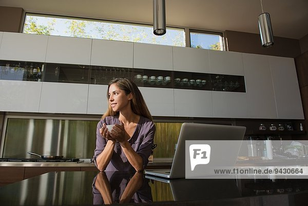 Mittlere erwachsene Frau im Esszimmer beim Kaffeetrinken