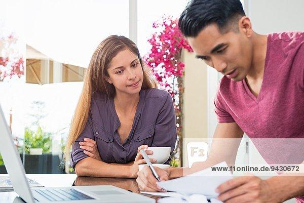 Besorgte Paare prüfen Rechnungen und Papierkram im Esszimmer