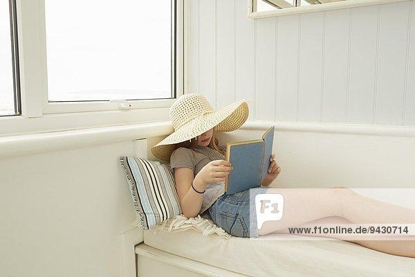 Mädchen in Sonnenhut auf der Veranda der Ferienwohnung lesen