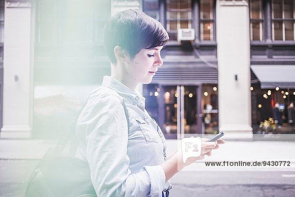 Woman using smartphone on street  New York  US