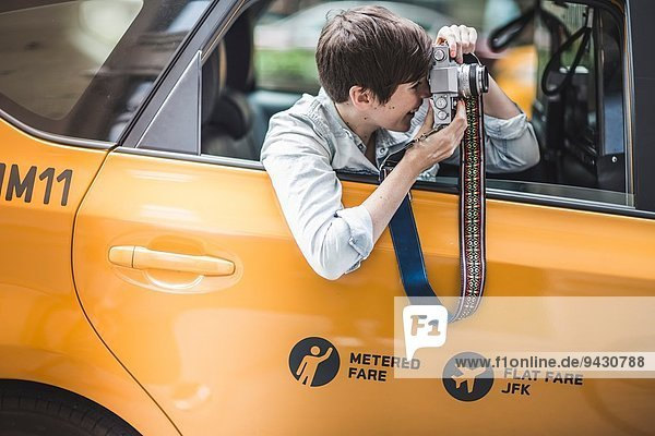 Woman photographing from yellow taxi  New York  US