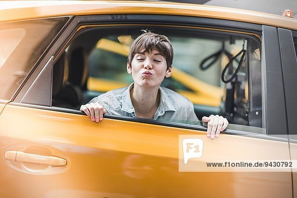 Woman blowing kiss from yellow taxi  New York  US