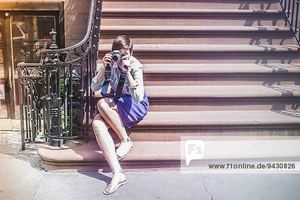 Photographer sitting on steps,  New York,  US