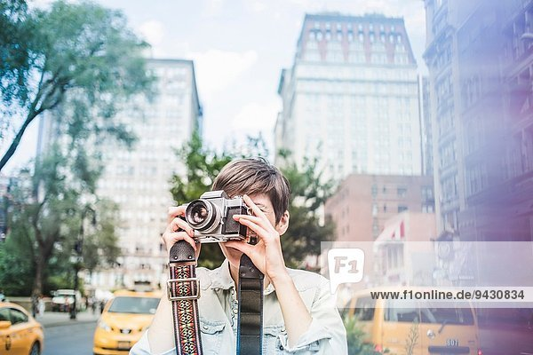 Young woman taking a picture,  New York,  US