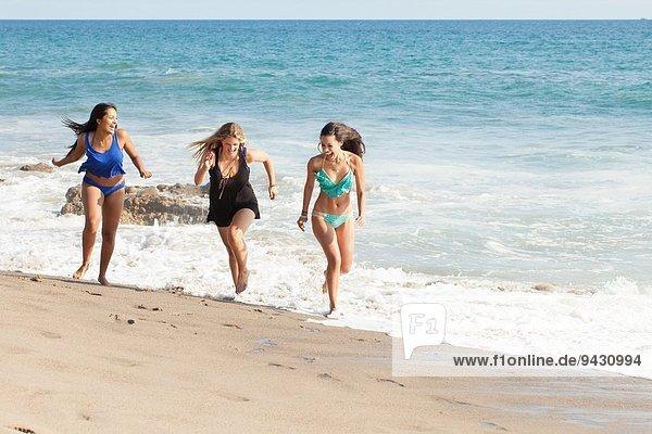 Drei junge Frauen laufen am Strand  Malibu  Kalifornien  USA