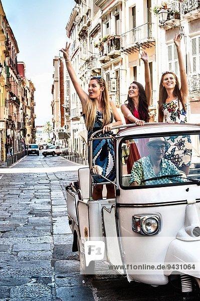 Drei junge Frauen winken vom offenen Rücksitz des italienischen Taxis  Cagliari  Sardinien  Italien