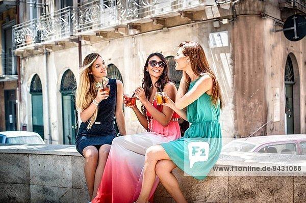 Drei junge  modische Freundinnen bei Cocktails auf dem Bürgersteig  Cagliari  Sardinien  Italien