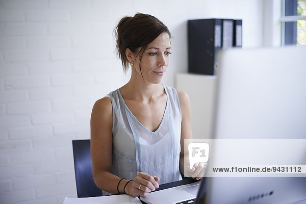 Mid adult woman working from home on computer