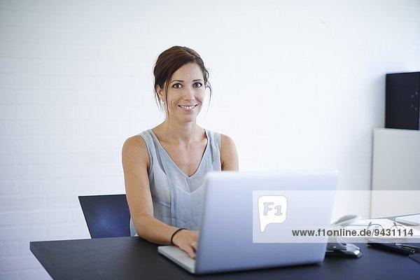 Portrait mittlere erwachsene Frau  die von zu Hause aus am Laptop arbeitet