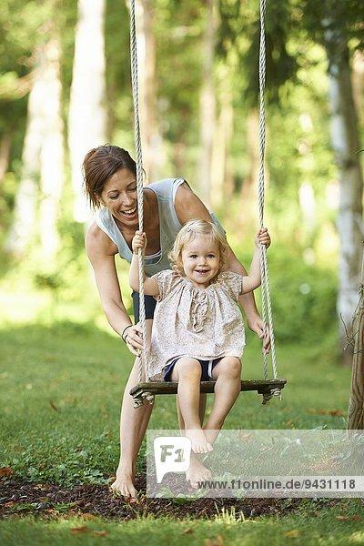 Mittlere erwachsene Mutter schiebt Kleinkind Tochter auf Gartenschaukel
