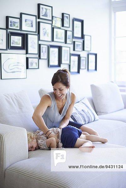 Mittlere erwachsene Mutter kitzelt Kleinkind Tochter auf Sofa