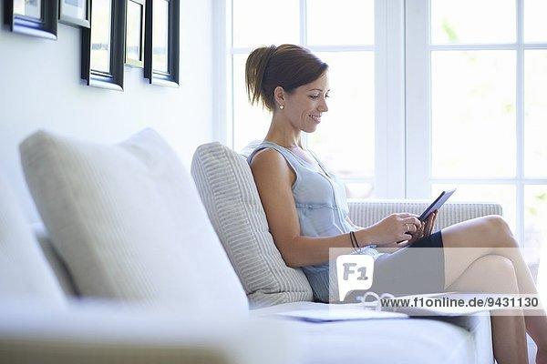 Mittlere erwachsene Frau mit digitalem Tablett auf dem Wohnzimmersofa