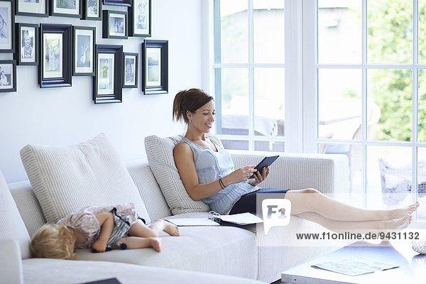 Mittlere erwachsene Frau mit digitalem Tablett auf dem Wohnzimmersofa  während die kleine Tochter schläft.