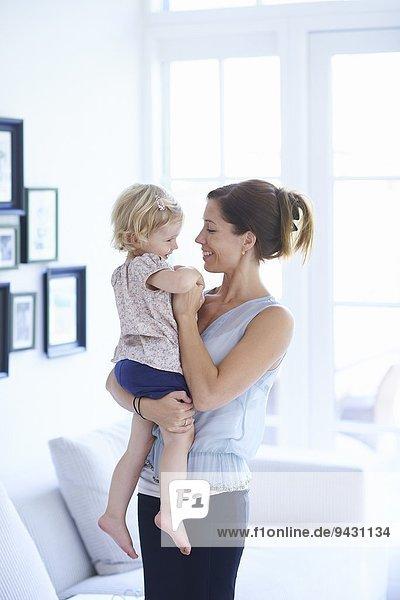 Mittlere erwachsene Frau und Kleinkind-Tochter im Wohnzimmer