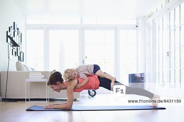 Mittlere erwachsene Mutter  die Yoga praktiziert  mit Kleinkind-Tochter auf dem Kopf.