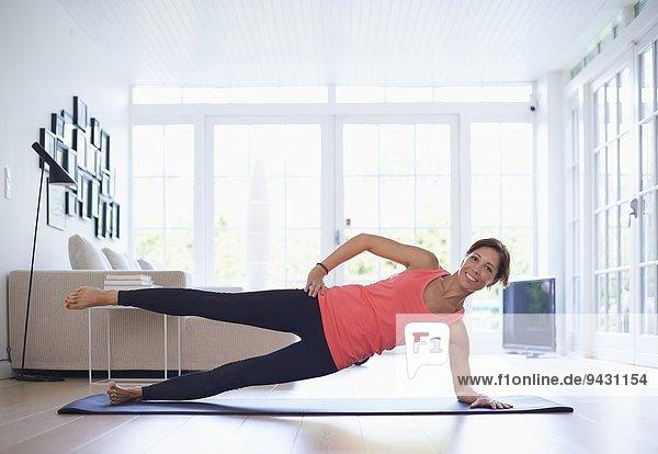 Mittlere erwachsene Frau praktiziert Yoga-Position im Wohnzimmer