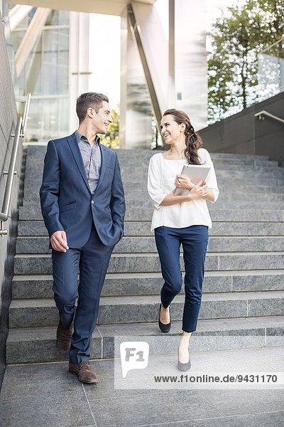Rückansicht des jungen Geschäftsmannes und der Frau  die die Treppe hinuntergehen  London  UK