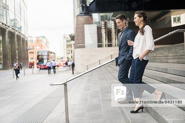 Rückansicht eines jungen Geschäftsmannes und einer jungen Frau  die sich beim Treppensteigen unterhalten  London  UK