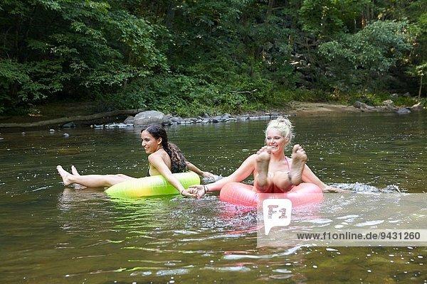 Frauen im Fluss mit aufblasbaren Ringen