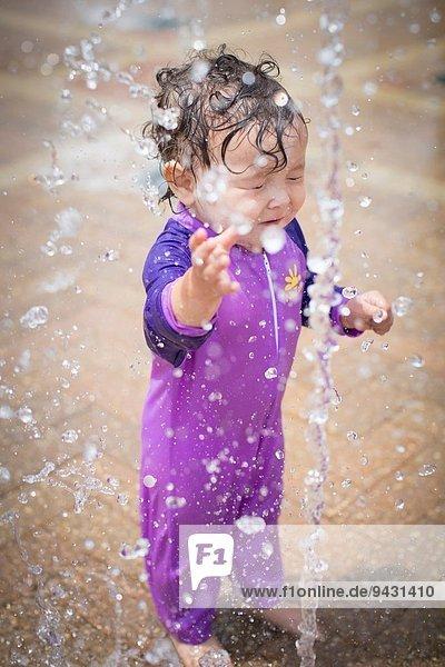 Süßes kleines Mädchen mit geschlossenen Augen  das mit Wasser besprüht wird. Süßes kleines Mädchen mit geschlossenen Augen, das mit Wasser besprüht wird.