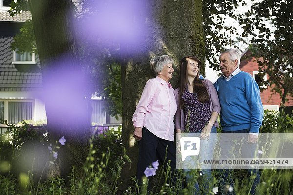 Grandparents and granddaughter standing by tree
