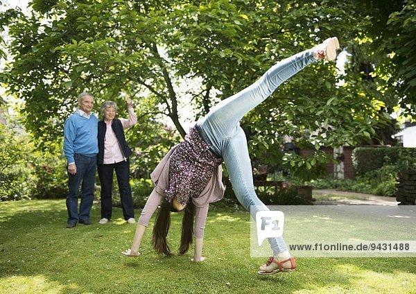 Grandparents and granddaughter doing acrobatics in garden