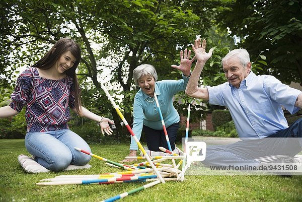 Grandparents and granddaughter playing giant pick up sticks