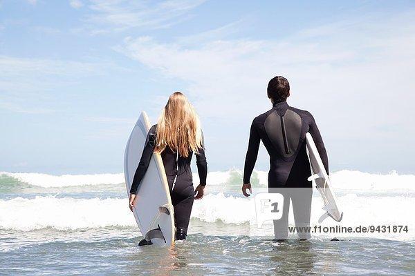 Junges Paar mit Surfbrettern auf dem Meer,  Rückansicht
