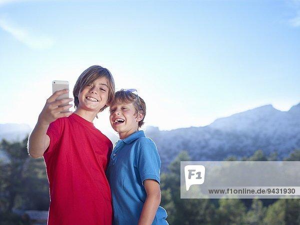 Two brothers taking selfie on smartphone  Majorca  Spain