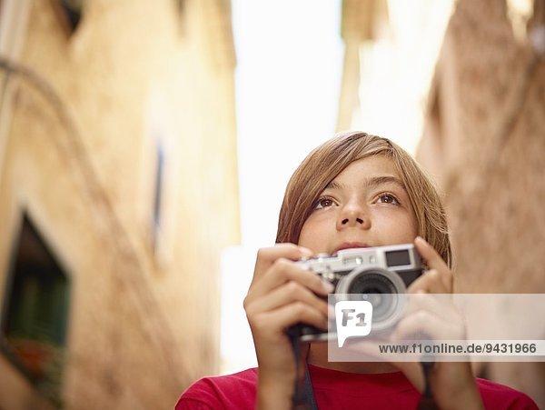 Close up of boy photographing village street using SLR camera  Majorca  Spain