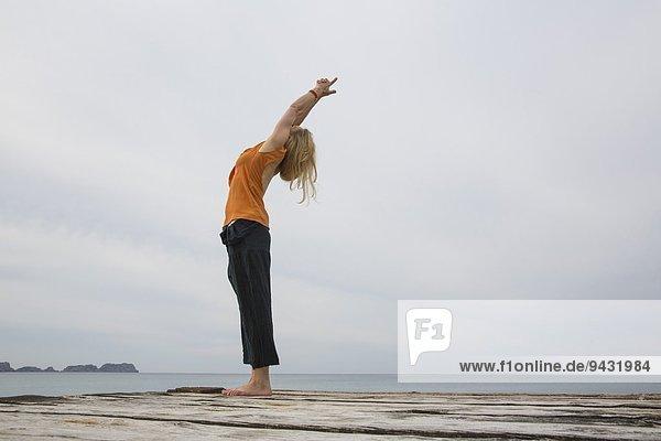 Mittlere erwachsene Frau  die sich zurückstreckt und Yoga auf einer hölzernen Seebrücke praktiziert.