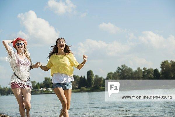 Zwei Freundinnen laufen am See entlang