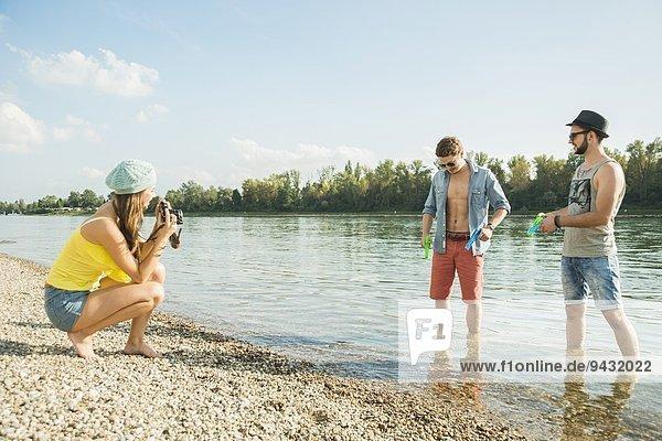 Junge Frau fotografiert Männer am See
