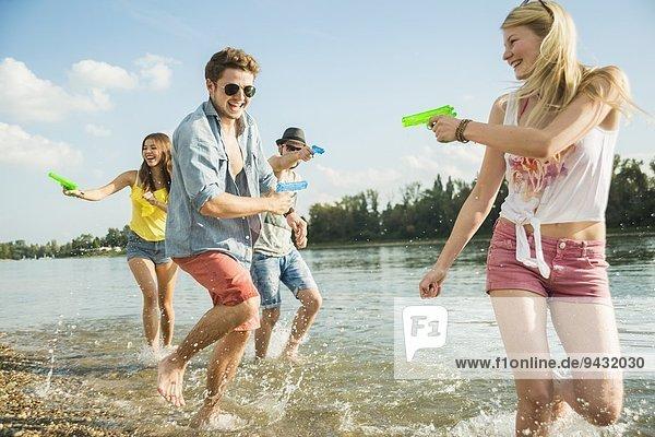 Freunde spielen mit Wasserpistolen im See